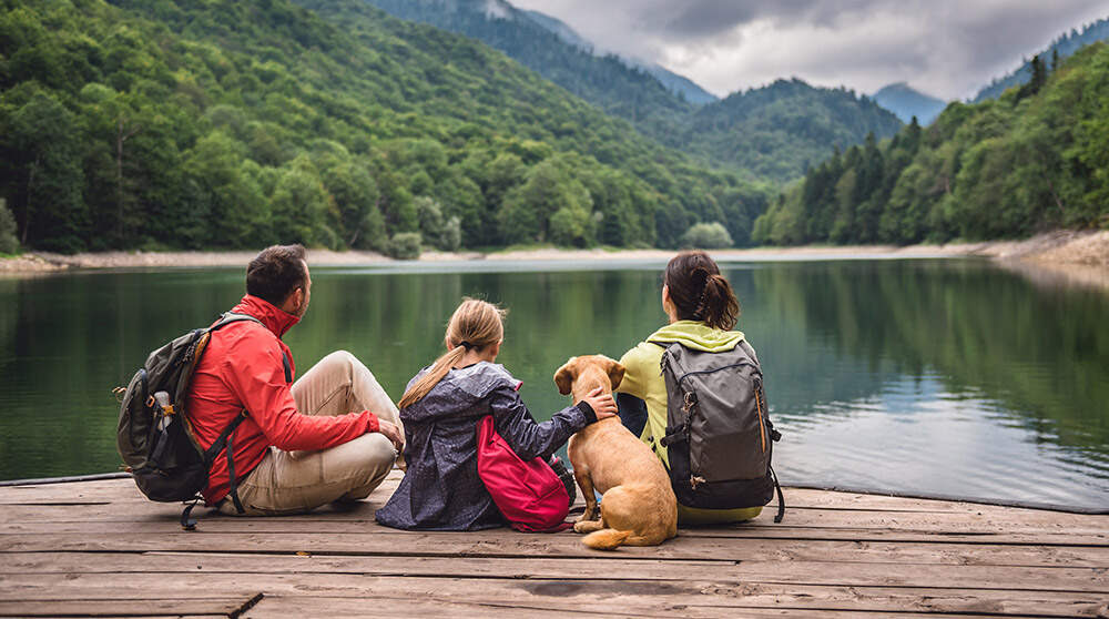 A family and their dog sit by a large body of water.