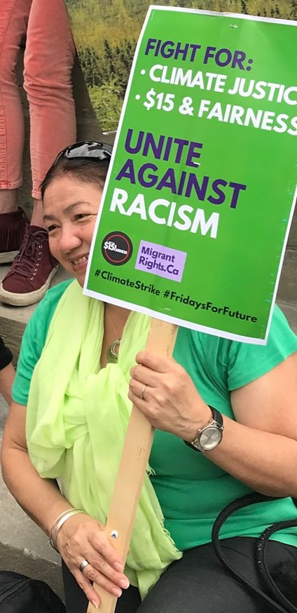 woman holds a green placard that says fight for climate and $15 & fairness, unite against racism