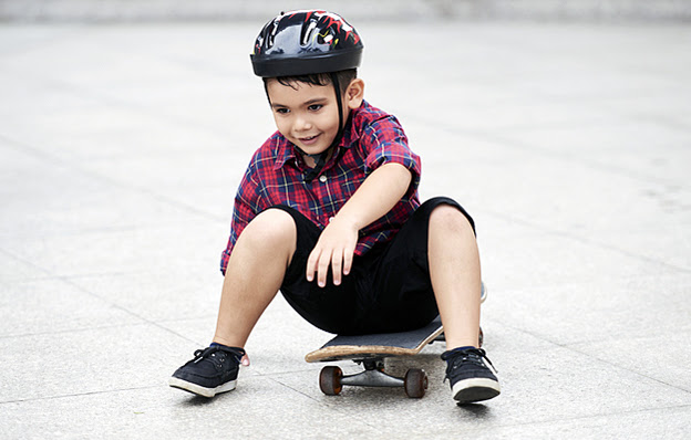 A young boy wearing a helmet sitting on a skateboard.
