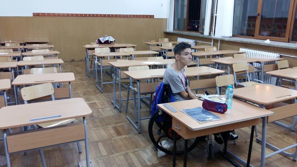 Åžtefan Stoain sits alone in a classroom