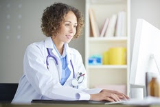 Image of a doctor in her office using a computer