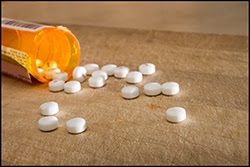 The figure above is a photograph showing pills spilling out from a bottle.