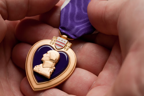 Man Holding Purple Heart War Medal in The Palm of His Hand.