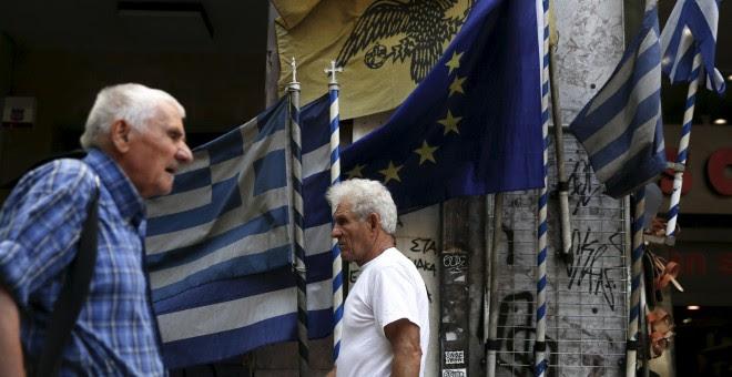 Dos hombres pasean en Atenas por delante de banderas griegas y europeas. /REUTERS