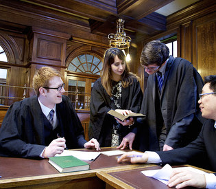 Image of 4 students in our Mock Court Room on Campus.
