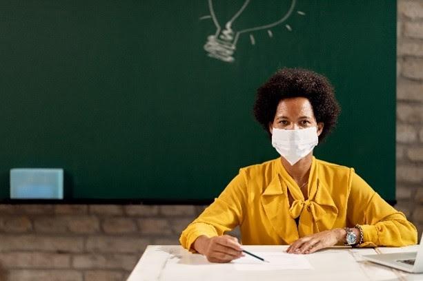 black teacher with mask at desk