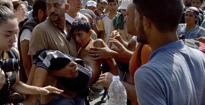 Refugiados llevan en brazos a un niño que se desmayó durante la larga espera para el procedimiento de registro en la isla griega de Lesbos. - EFE