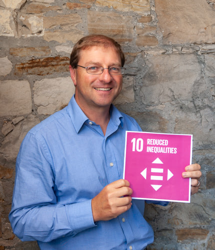 Photo of Paul, a white man in a blue shirt with glasses, holding up a sign that reads '10 - Reduced Inequalities'