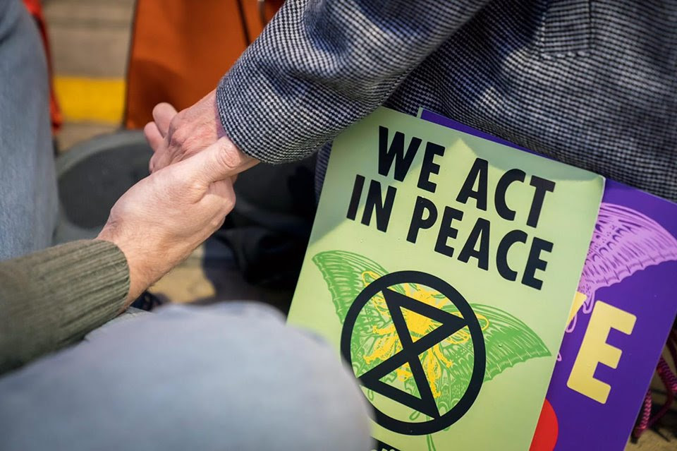Tow people hold hands with the sign we act in peace,