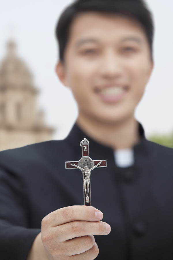 Young Priest Holding Crucifix, Looking at Camera