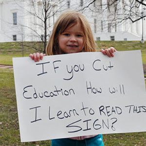 girl holding sign about                                           education funding