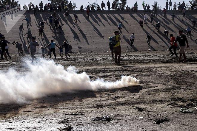 Manifestantes huyen del ataque con gases lacrimógenos de los elementos de la USBP (border patrol) al territorio mexicano