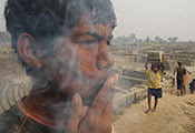 Teenage boy smokes bidi cigar outdoors in India