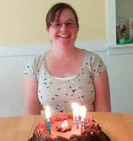 Erin smiling with a birthday cake.