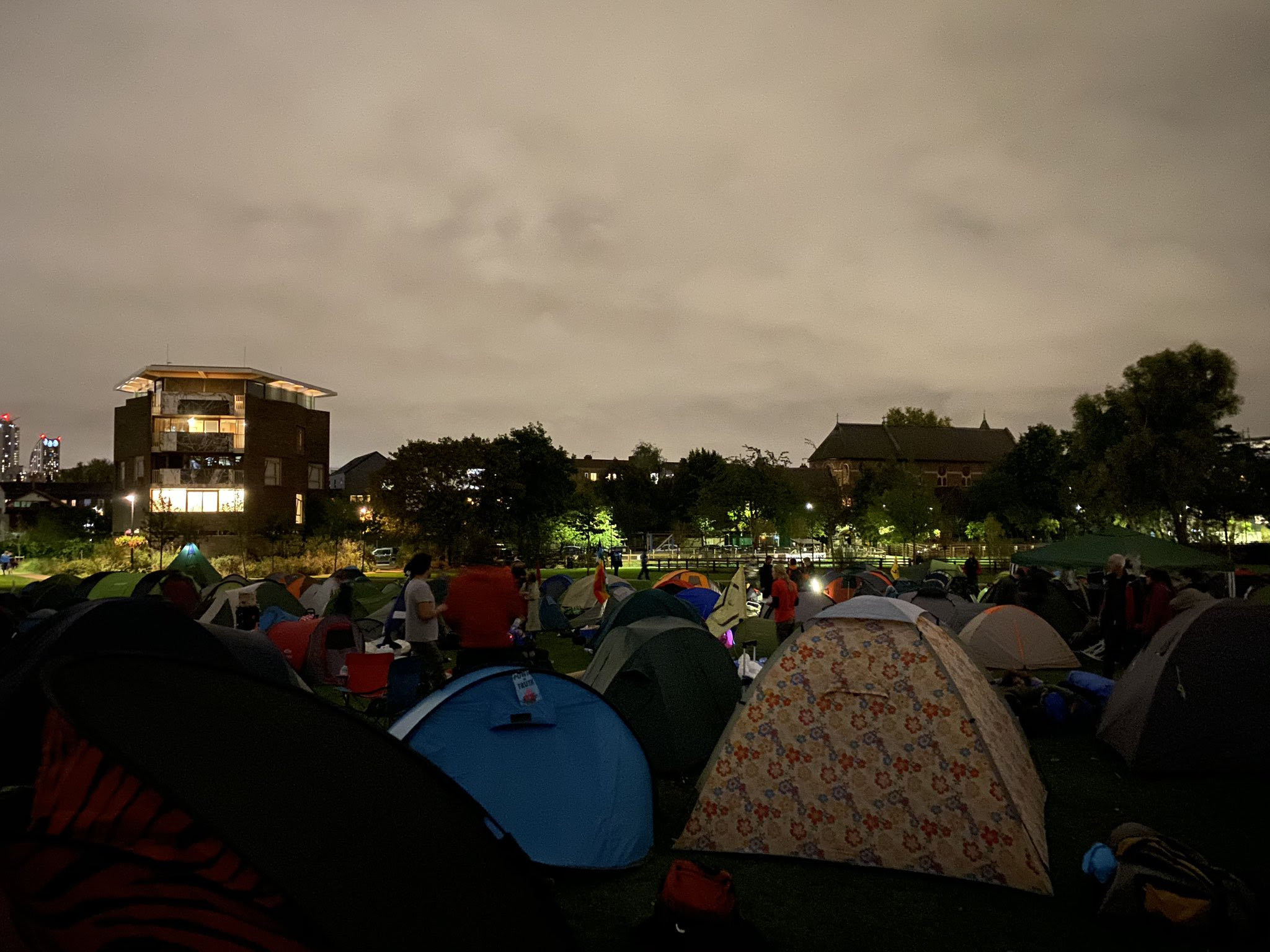 Around 30 tents in a field (Vauxhall Pleasure Gardens) at dusk.