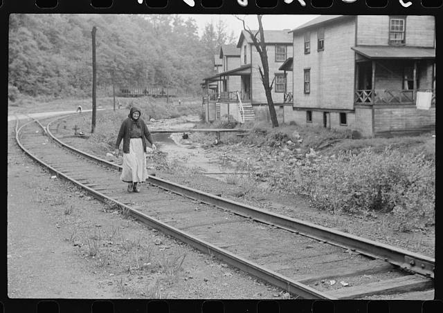 Woman (probably Hungarian) coming home along railroad tracks in coal mining town, company houses at right, Pursglove, Scotts Run, West Virginia