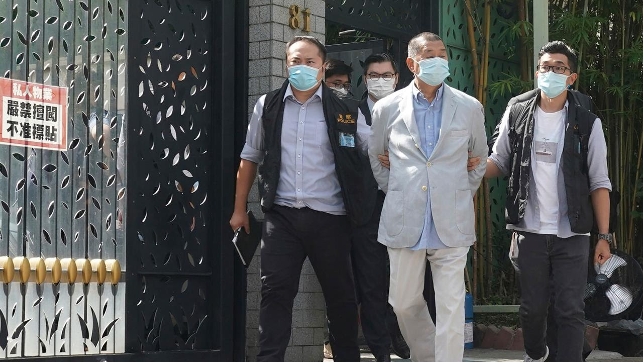 Hong Kong media tycoon Jimmy Lai, center, is arrested by police officers at his home in Hong Kong, Aug. 10, 2020.