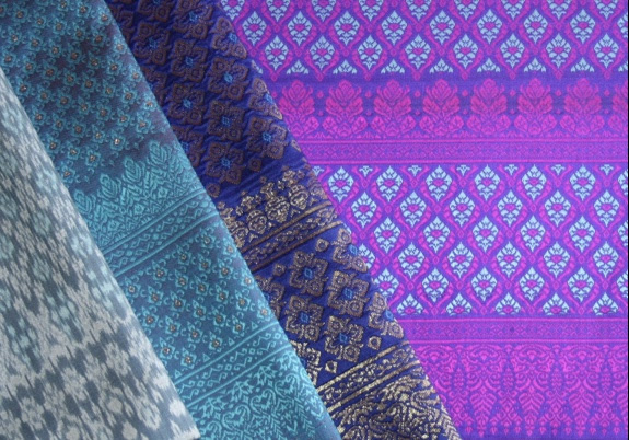 Look at the two narrow bands in the border design on the bottom of each of the three lengths of brocade (right of the aqua ikat). They're known as Banteay Srei Stripes.