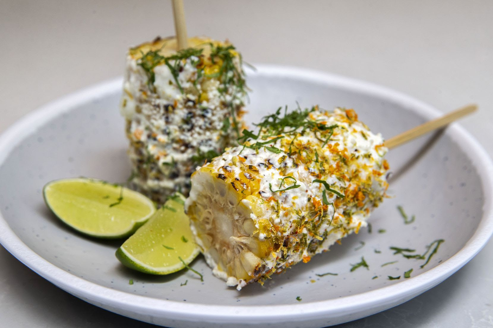 Elote on a Stick is topped with ricotta, cotija, chili-citrus sprinkle and cilantro, with lime on the side.