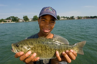 boy holding a bass on Lake St. Clair
