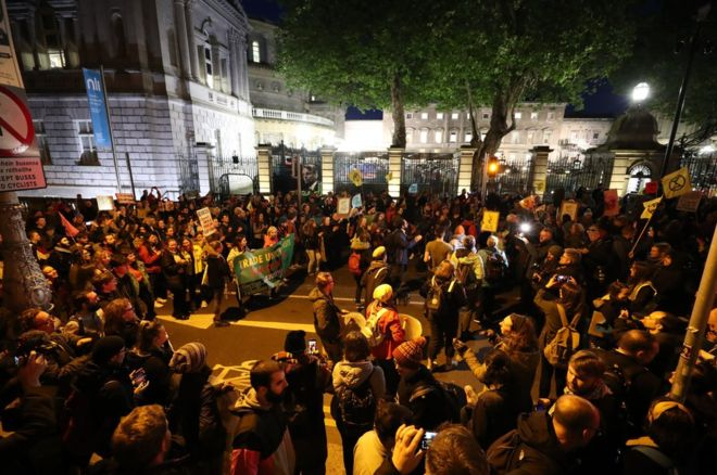 Hundreds of rebels outside the gates of the Irish parliament at night.
