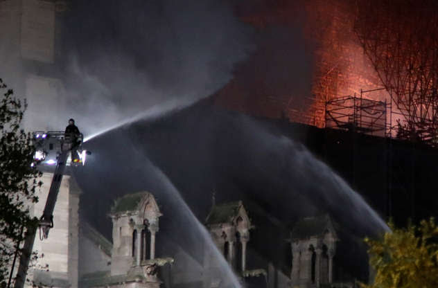Slide 7 of 31: Fire fighters douse flames of the burning Notre Dame Cathedral in Paris, France April 15, 2019. REUTERS/Charles Platiau