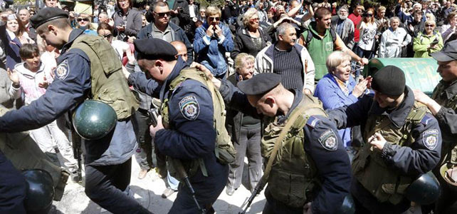 Policías ucranianos avanzan en fila india mientras prorrusos retoman el control de un edificio administrativo en Mariupol. - REUTERS