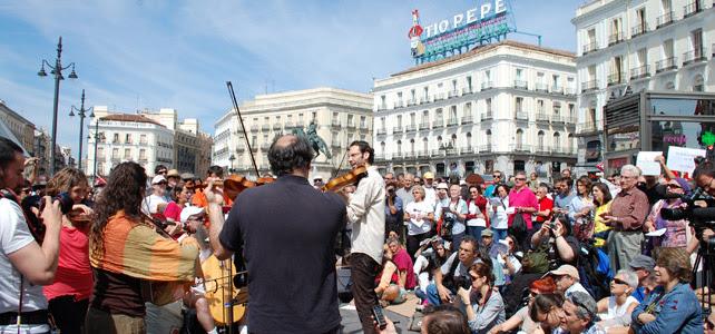 Varias personas escuchando la actuación de la Solfónica en la Puerta del Sol
