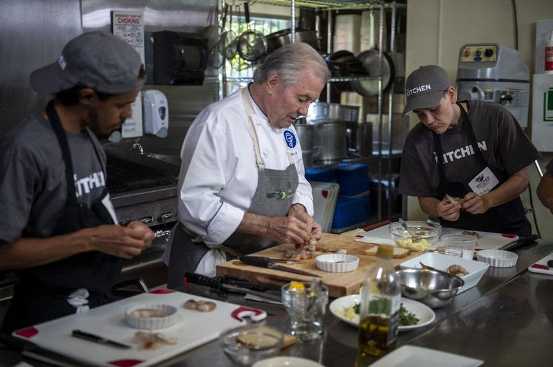 Student Nathaniel Rivera (left) and Ruby VanGuilder (right) watch as Jacques Pepin demonstrates how to clean shrimp during a filmed culinary training demonstration by chef Pepin at The Kitchen Friday, Aug. 2, 2019, in Hartford.