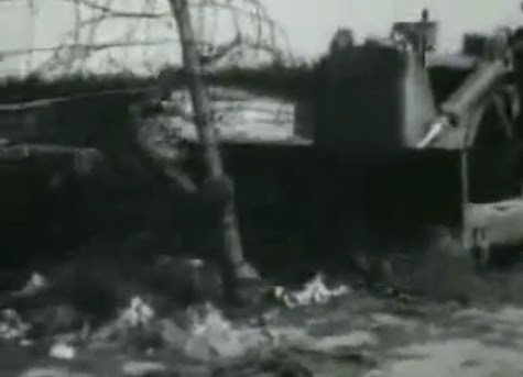 A bulldozer flattening Bergen Belsen camp                         cutting the barbed wire fence (27min. 58sec.)