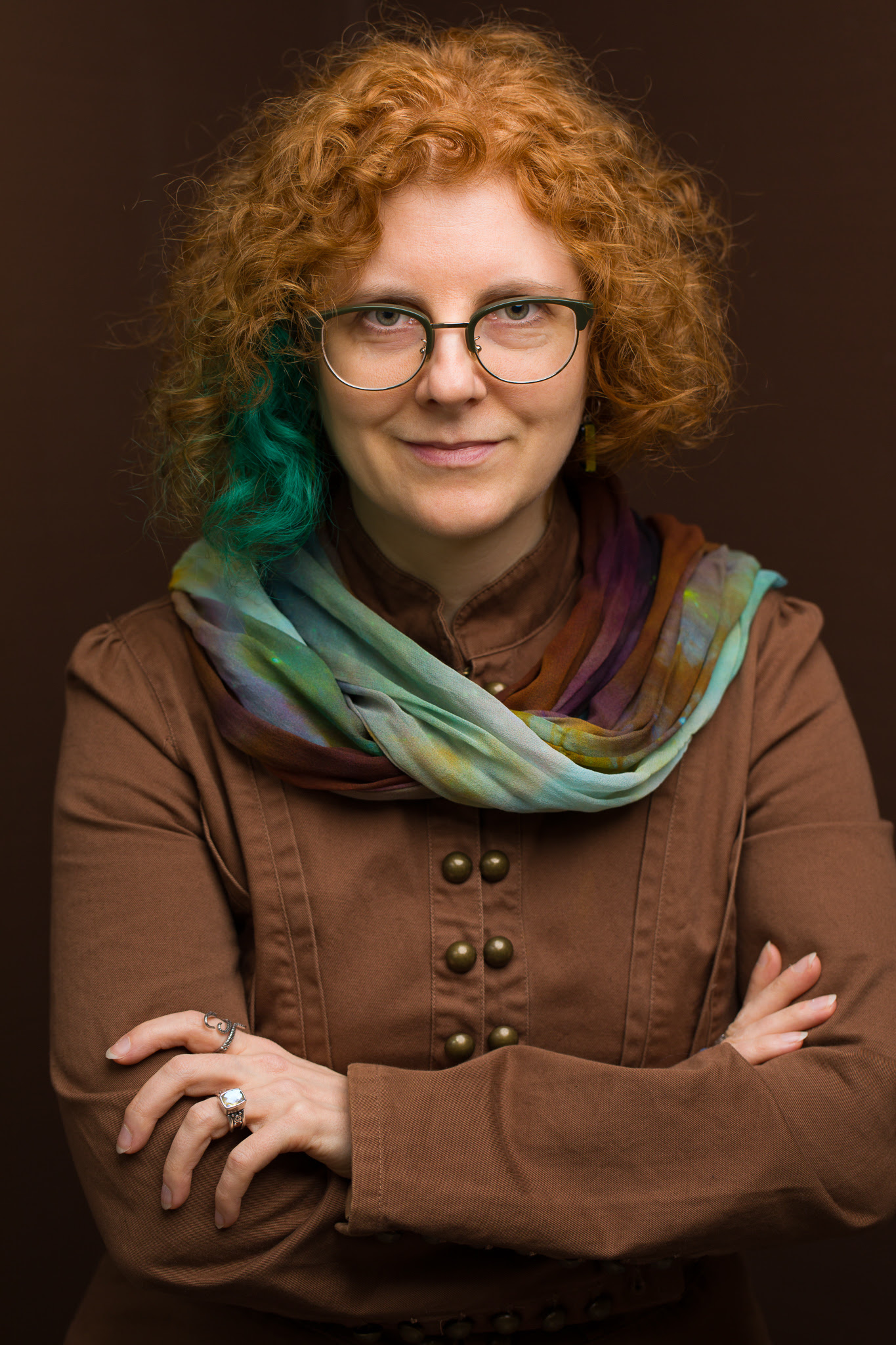 Photo of Dora Raymaker, a white person with red curly hair with one section dyed green. They are wearing a brown jacket and a green and brown scarf in front of a brown background.