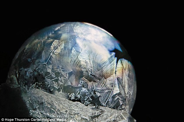 Reflections: This                                                  remarkable ice bubble                                                  looks like a frozen                                                  planet hanging in                                                  starless space