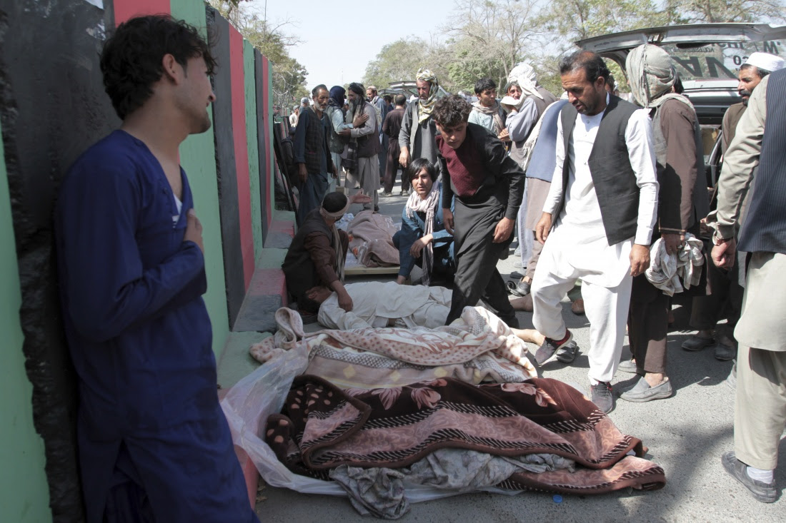 Afghan villagers stand over bodies of civilians during a protest
