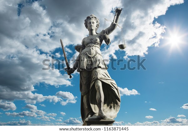 Justitia symbol of justice in front of background with sky and clouds. Concept of justice and law.