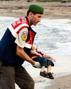 Un agente de la gendarmería turca lleva el cuerpo de un niño que formaba parte del grupo de refugiados sirios que se han ahogado intentando llegar a la isla de Kos. REUTERS/Nilufer Demir