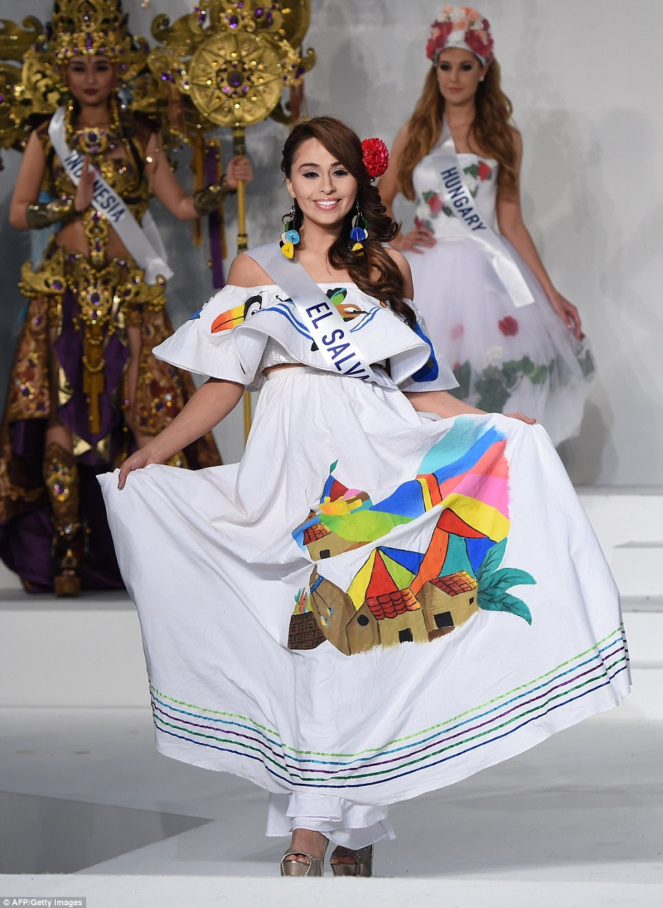 El Salvador kept things simple with Eugenia Avalos wearing a white cotton dress depicting vibrant scenes of a classic country landscape, as well as pottery and a colourful toucan