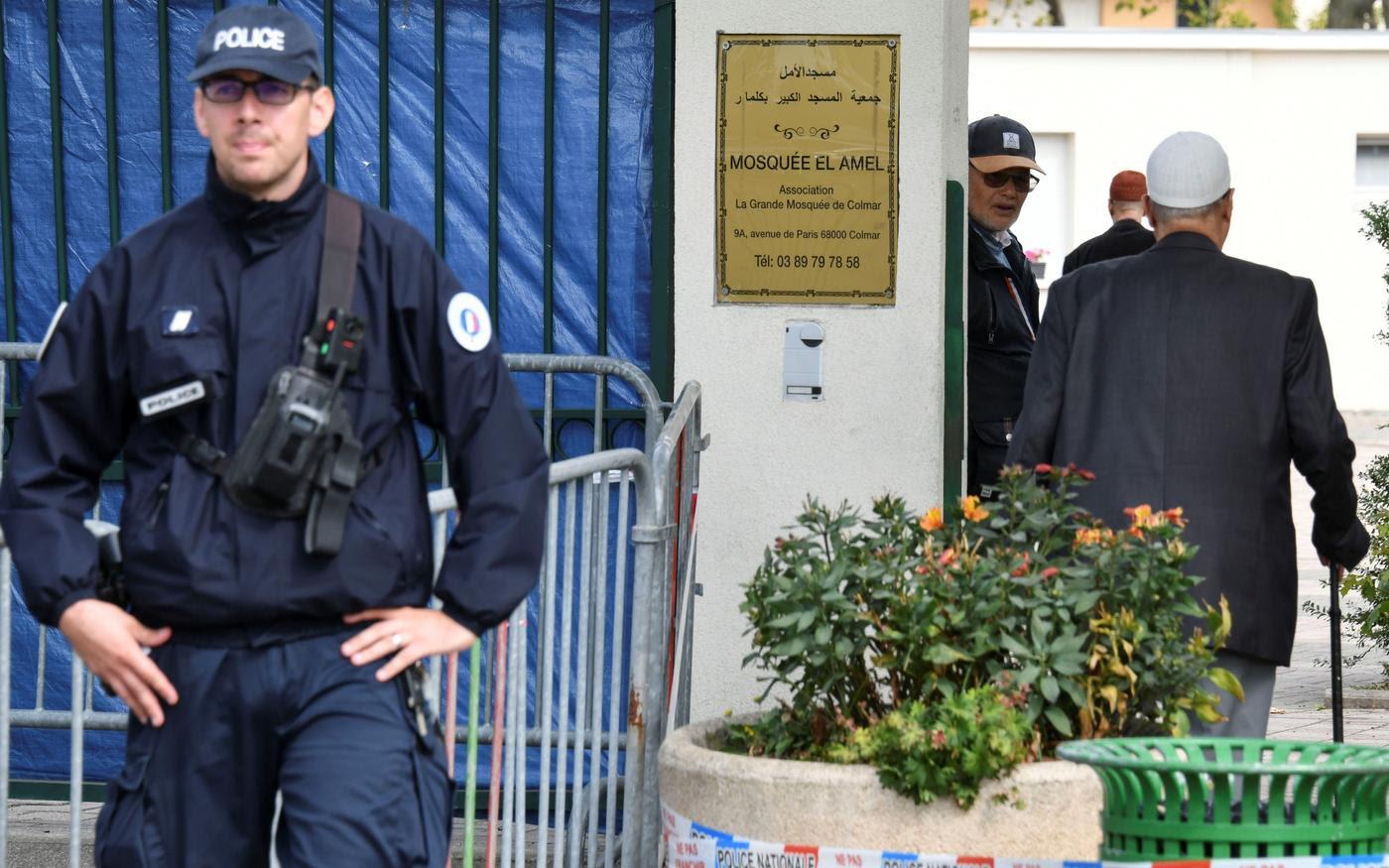 Des fidèles arrivent à la grande mosquée de Colmar, dans l'est de la France, où un policier monte la garde, le 22septembre2019 (AFP)