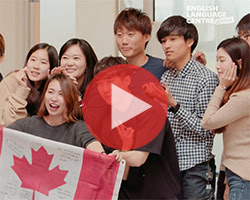 Students smiling and holding Canadian flag