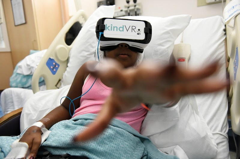 A young girl reaches towards the direction of the camera while wearing a VR headset in a hospital bed