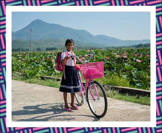A young girl walking a bike in front of a green field and mountain range.
