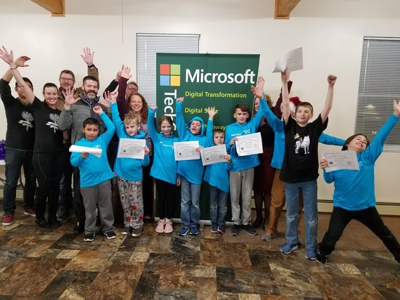 A mix of elementary and middle school students hold their Hour of Code completion certificates and raise their hands in excitement with State Superintendent Jillian Balow, and staff from Microsoft and the Array School of Technology and Design. They are all standing in from of a Microsoft banner.