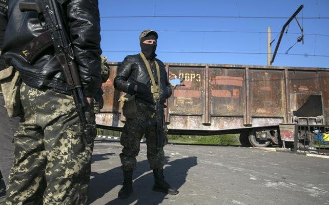 Prorrusos armados vigilan un puesto de control junto a una vía de tren en Slaviansk.