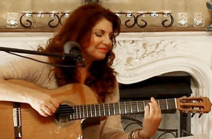 Elaine Lucia singing and playing guitar in front of beautiful white fireplace