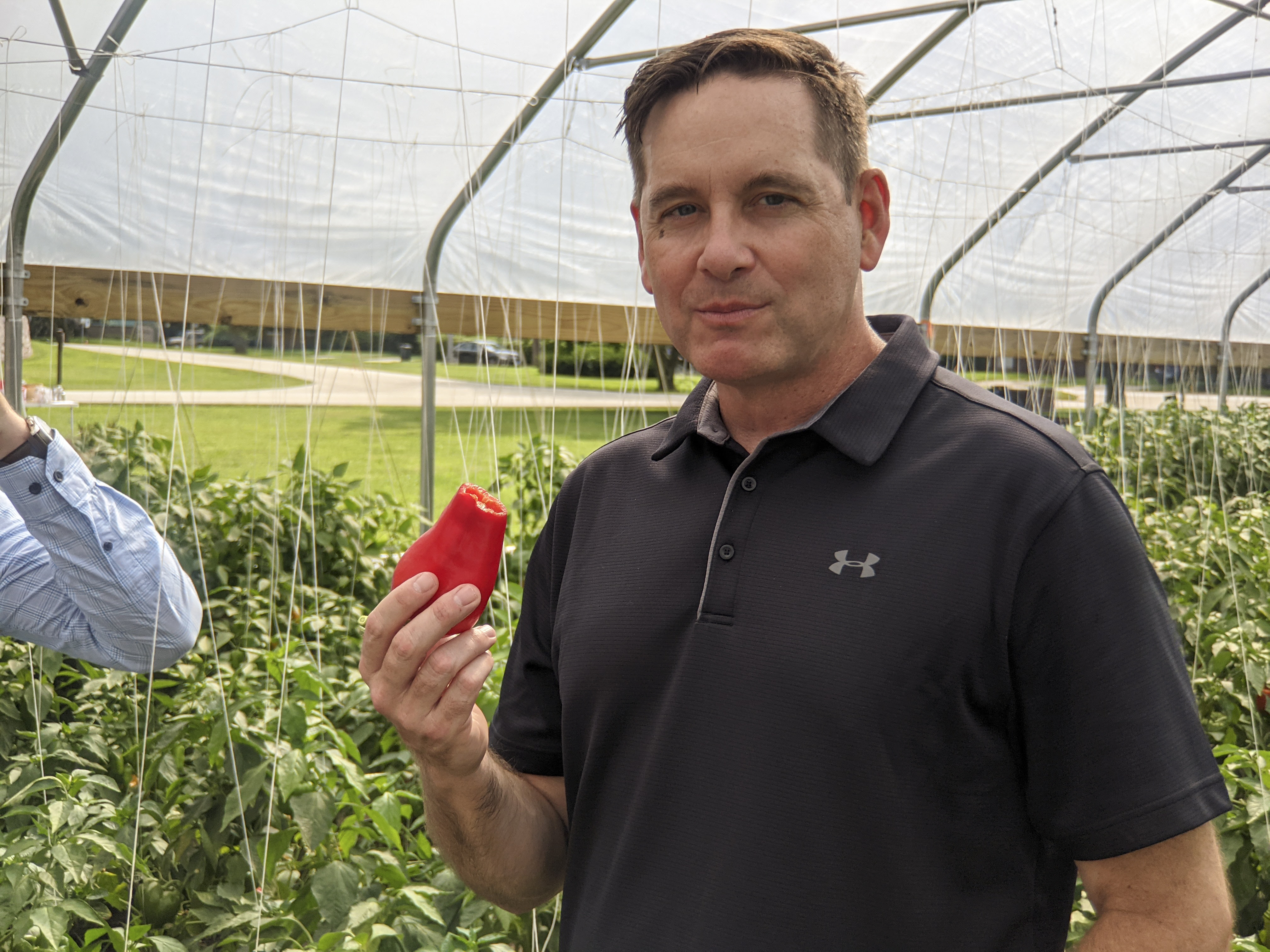 State Rep Tim Butler smiles at the camera after a tasty bite of sweet red pepper grown in the hoop house he's photographed in.