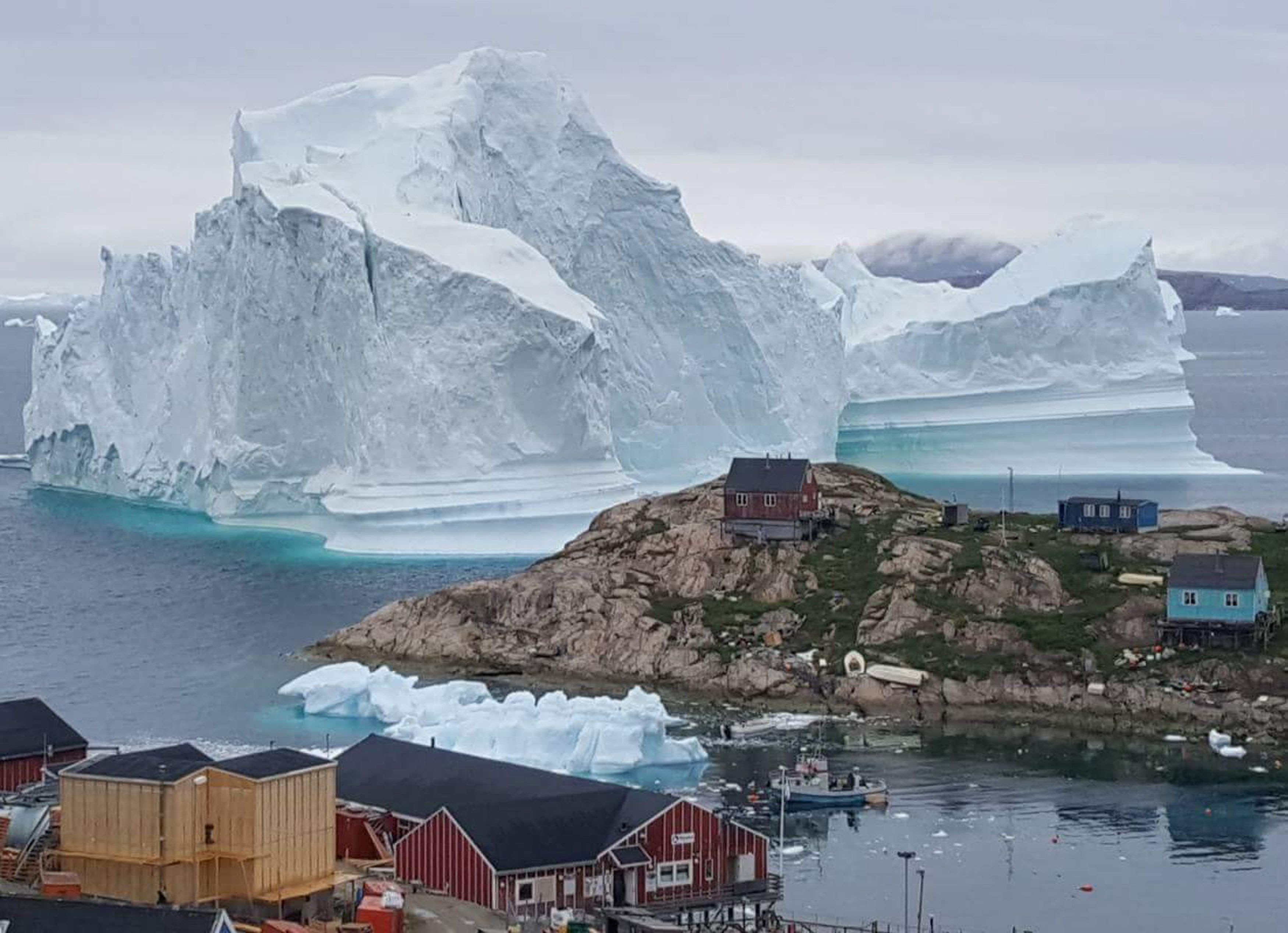 DENMARK OUTMandatory Credit: Photo by KARL PETERSEN/EPA-EFE/REX/Shutterstock (9760878a)A general view shows an iceberg stranded near the village of Innaarsuit, in the Avannaata Municipality, northwestern Greenland, 12 July 2018 (issued 13 July 2018). The Avannaata Municipality was alarmed on 11 July, after a huge iceberg was grounded just outside the village of Innaarsuit. According to local media, police asked villagers who live closest to the water, to leave their houses over fears the iceberg could calve and affect the village with a tsunami.Iceberg grounded outside village in northwestern Greenland, Innaarsuit - 12 Jul 2018