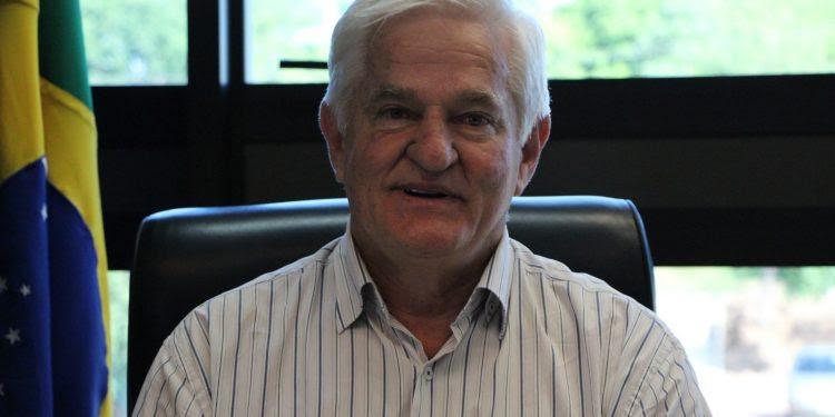 Antonio Galvan é um senhor branco com cabelos grisalhos. Na foto veste camisa social branca listrada. Ao seu lado está uma bandeira do Brasil.