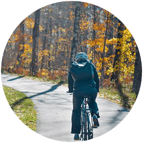 A bicyclist surrounded by colorful fall trees