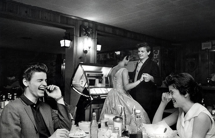 Phil Everly: Don Everly sits laughing at the table while Phil dances with a friend to th