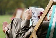 A Veteran doing a crossword puzzle in his backyard