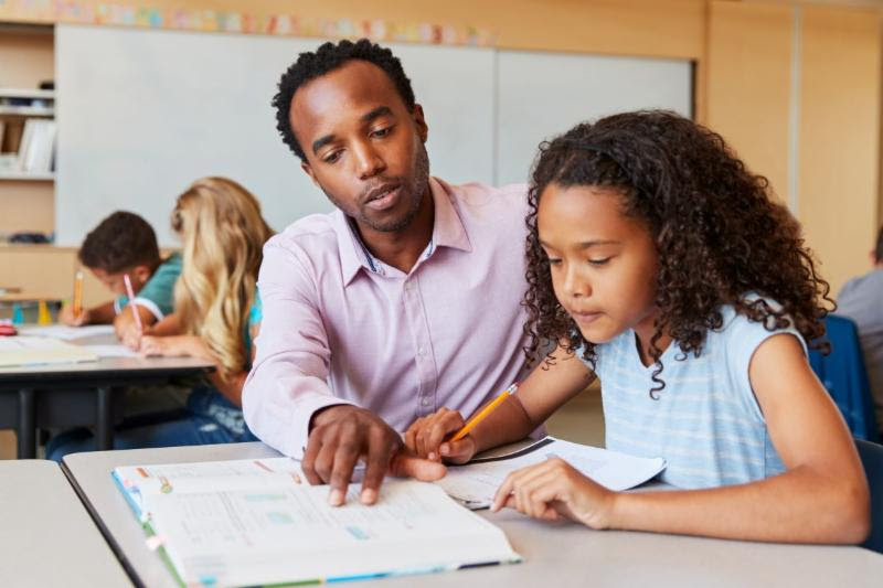 teacher helping a student in the classroom